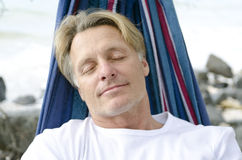 Man sleeping in hammock. A color portrait photo of a mature blonde man in his forties sleeping peacefully in a hammock at the beach Royalty Free Stock Photography