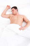 Man sleeping in his bed at home with one hand on pillow. Young caucasian half naked man sleeping in his bed at home with one hand on pillow,  domestic atmosphere Stock Photography