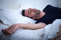 Man sleeping in his bed and snoring. Loudly Stock Photo