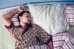 Man sleeping in his bed on white pillow. Single man sleeping soundly in her bed Stock Images
