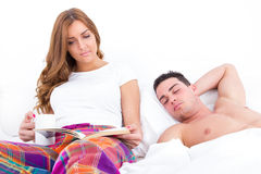 Man sleeping while his girlfriend is reading in bed. Man sleeping while his girlfriend is reading book and having coffee in bed royalty free stock photography