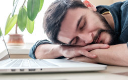 Man sleeping with his laptop. Bearded man sleeping at his working place home office with head on the desk Stock Images