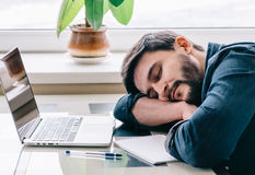 Man sleeping with his laptop. Bearded man sleeping at his working place home office with head on the desk Royalty Free Stock Photos