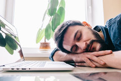 Man sleeping with his laptop. Bearded man sleeping at his working place home office with head on the desk Stock Photo