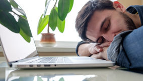 Man sleeping with his laptop. Bearded man sleeping at his working place home office with head on the desk Royalty Free Stock Photography