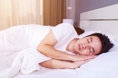 Man sleeping with his wife in a comfortable bed at home Stock Photography
