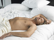Man Sleeping In Hotel Bedroom Stock Photo