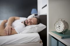 Free Man Sleeping In His Bedroom With Alarm Clock In Foreground Stock Photo - 157928450