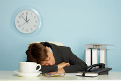 Man sleeping on the job. Tired man sleeping on a table next to mug and phone Royalty Free Stock Images