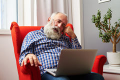 Man sleeping with laptop on the red chair at home. Bearded senior man sleeping with laptop on the red chair at home Royalty Free Stock Image