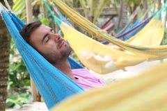 Man sleeping in large hammock area stock photography