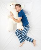 Man sleeping with large teddy bear. Young man sleeping in an embrace with a large white teddy bear. Top view photo Royalty Free Stock Image
