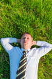 Man sleeping on the lawn. Man in a tie sleeping on the lawn Stock Photo