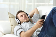 Man sleeping listening music at home. Man sleeping while is listening music lying on a sofa in the living room at home Royalty Free Stock Image