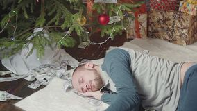 A man is sleeping with a lot of dollars and a Christmas tree. A man with a lot of dollars wakes up after Christmas stock footage
