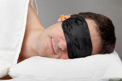 Man with Sleeping mask and earplugs in bed. Man with Sleeping mask and earplugs lying in bed Stock Photography