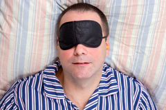 Man sleeping with a mask on eyes. Man sleeping in bed with a mask on eyes Royalty Free Stock Photo