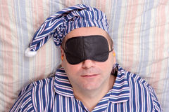 Man sleeping with a mask on eyes. Man sleeping in bed with a mask on eyes Stock Photography