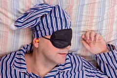 Man sleeping with a mask on eyes. Man in pajamas sleeping with a mask on eyes in the bed Royalty Free Stock Image