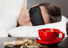 Man with Sleeping mask sleep in bed. Man with Sleeping mask sleep on a bed, cup of herbal tea in the foreground. Focus on tea cup Stock Photography
