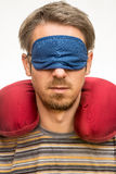 Man with sleeping mask and travel pillow Stock Photography