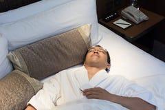 Man sleeping. Mature Asian man in bathrobe in hotel, sleeping on bed Stock Images