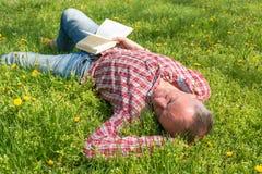 A man sleeping on a meadow Stock Photos