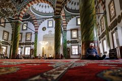 Man sleeping in a mosque leaning against a pilar stock image