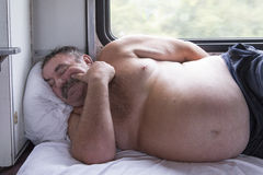 Man sleeping in naked upper body in the train,russian federation. Man sleeping in naked upper body in the train is taken in russian federation stock photo