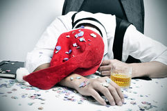 Man sleeping in the office after a christmas party. A man with a santa hat and covered with confetti sleeping in his desk after an office christmas party Stock Photos
