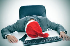 Man sleeping in the office after a christmas party. A man in suit with a santa hat sleeping in his desk after an office christmas party Royalty Free Stock Image