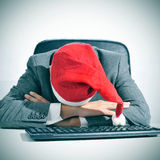 Man sleeping in the office after a christmas party. A man in suit with a santa hat sleeping in his desk after an office christmas party Stock Images