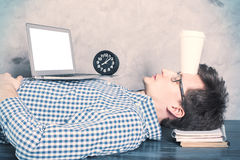 Man sleeping on office desk. Young caucasian guy with blank white laptop screen sleeping on office desktop with coffee cup on forehead. Mock up Stock Photography