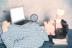 Man sleeping in office. Young caucasian businessman with blank white laptop screen sleeping on desktop with coffee cup on forehead. Mock up Royalty Free Stock Photo