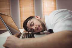 Man sleeping in office. Young man sleeping on desk in office Royalty Free Stock Image