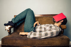 Man sleeping on old sofa with book covering his face Stock Photography