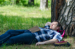 Man is sleeping with open book in pine forest at old pine. Man is sleeping in pine forest at old pine with open book lying on his stomach royalty free stock image