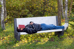 Man Sleeping Outside. A young man sleeping on a park bench with a book over his face Royalty Free Stock Photography