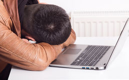 Man sleeping over laptop Stock Image