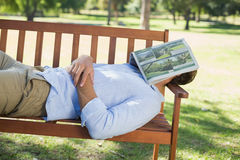 Man sleeping on park bench with newspaper over face. On a sunny day Royalty Free Stock Photography