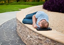 Man sleeping in a park with laptop as pillow Royalty Free Stock Photo