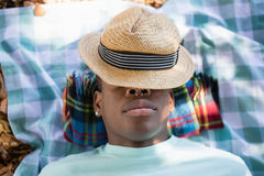 Man sleeping on picnic blanket with hat on his face Royalty Free Stock Photo