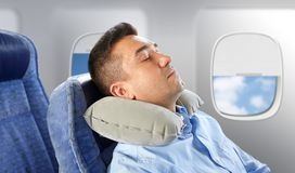 Man sleeping in plane with cervical neck pillow. Travel, comfort and people concept - men sleeping in plane with inflatable cervical neck pillow over porthole Royalty Free Stock Images