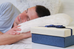 Man sleeping with present on bed pillow close up. Selective focus on gift box. Surprise birthday gift Stock Photography