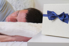 Man sleeping with present on bed pillow close up. Selective focus. Surprise birthday gift Stock Photography