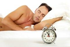 Man sleeping, retro alarm clock. Attractive caucasian middle aged man sleeping and a retro alarm clock showing midnight. Focus on clock. Studio shot. White Stock Images