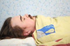 Man sleeping rolled in blanket Stock Image