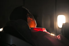 Man sleeping in the seat. Of an aircraft in sunrise Royalty Free Stock Photos