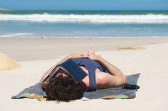 Man sleeping on secluded beach with book covering face Stock Photos