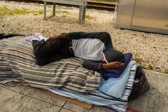 Man sleeping on sidewalk Stock Images